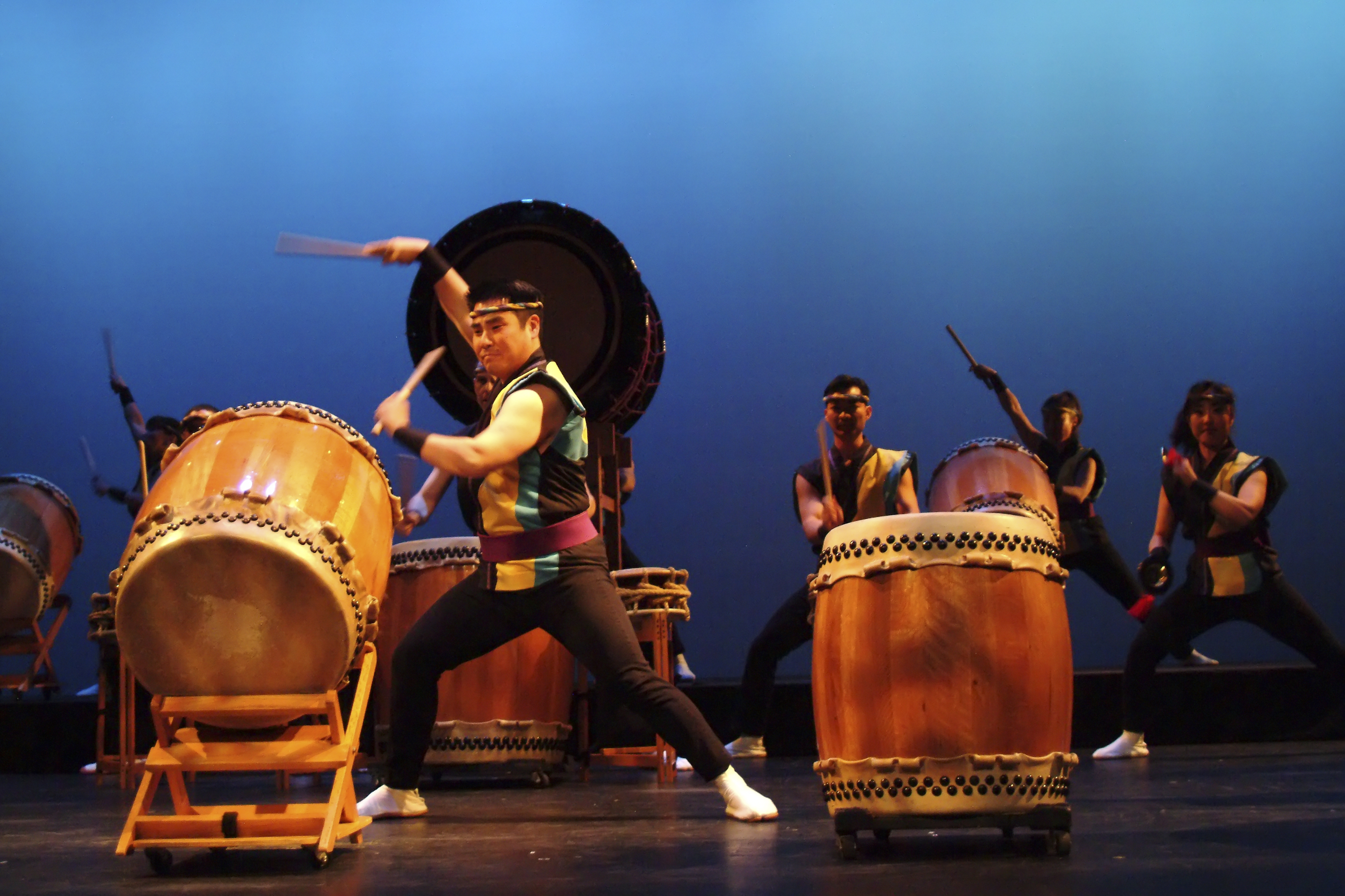 A group of performers playing on japanese taiko drums