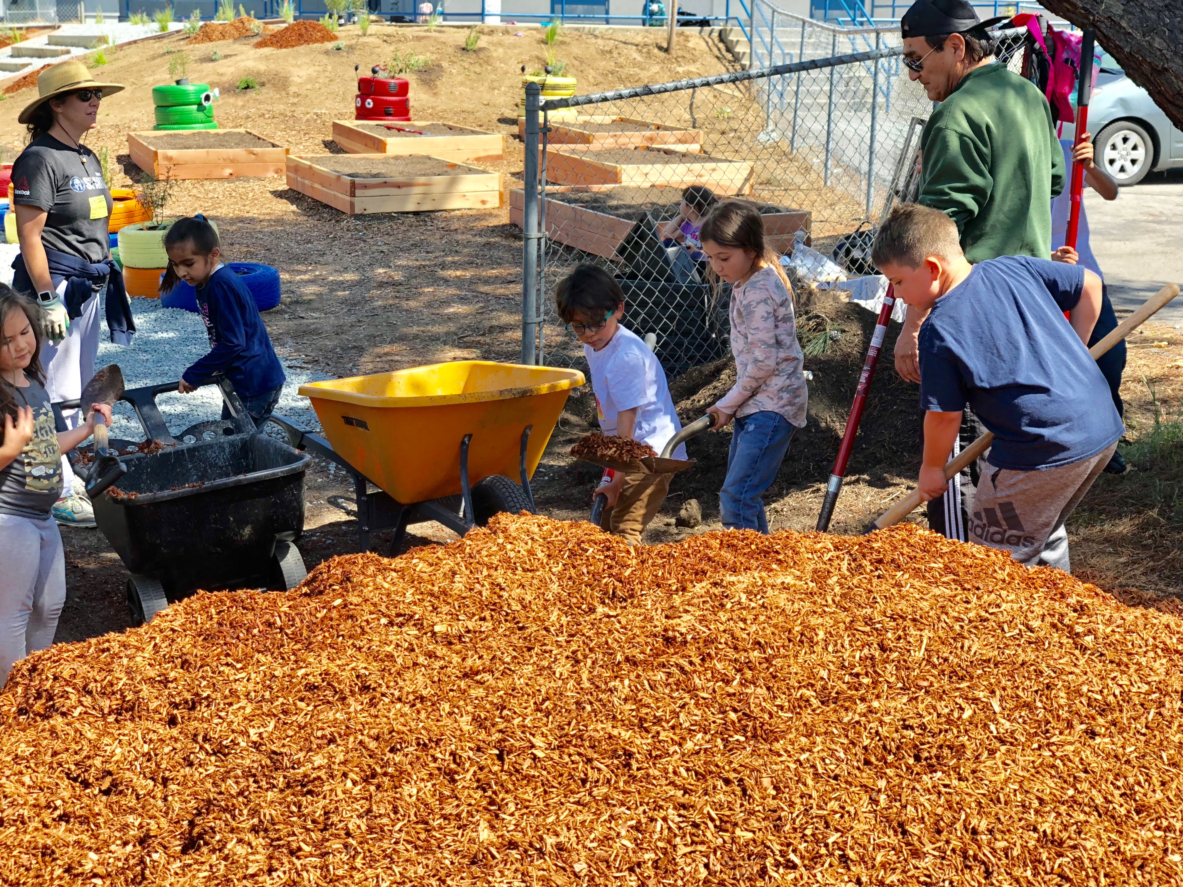 Children shoveling mulch